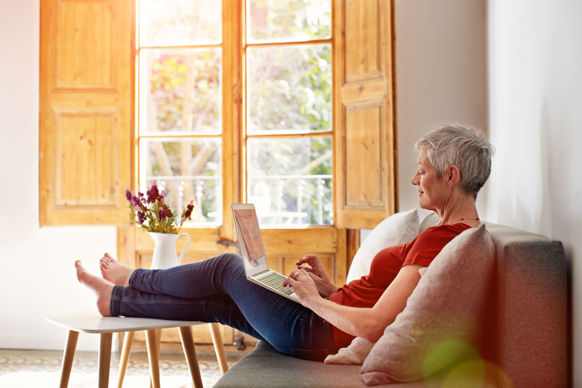 Senior woman relaxing on a couch with her laptop