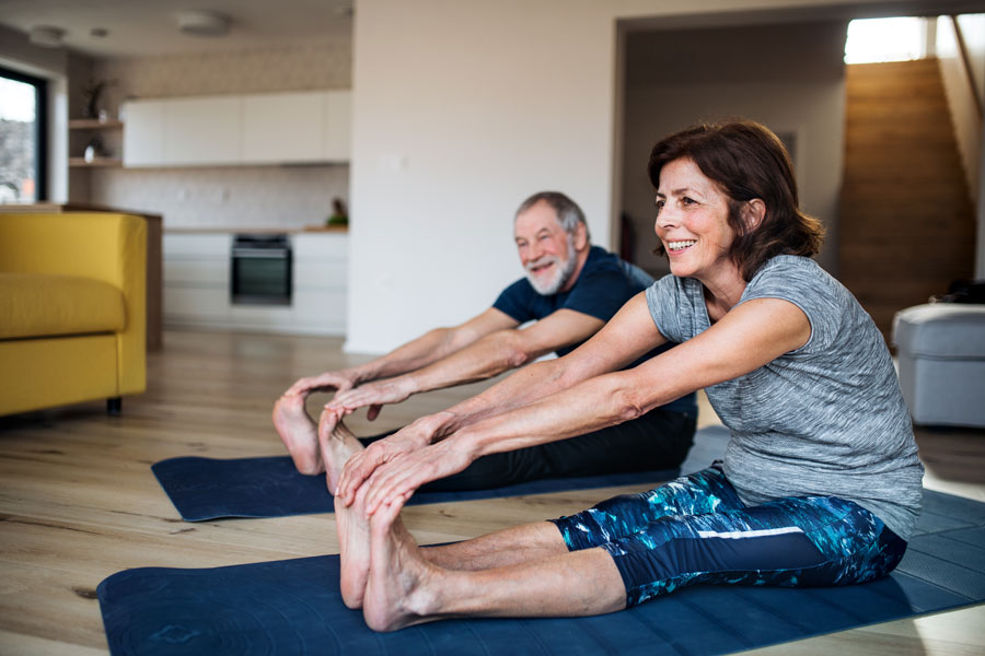 Senior man and woman stretching before exercising at a yoga class.